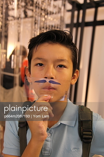 Boy pretending to have a mustach - p664m2087193 by Yom Lam