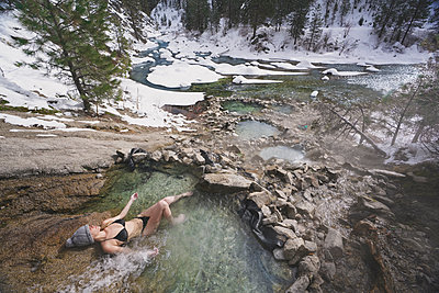 High angle view of woman wearing bikini while relaxing in thermal pool at forest during winter - p1166m2011743 by Cavan Images