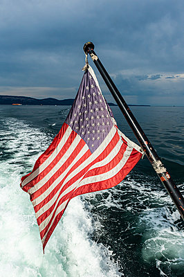 USA,Washington,American flag on back of moving motorboat - p300m2203003 by Michael Runkel