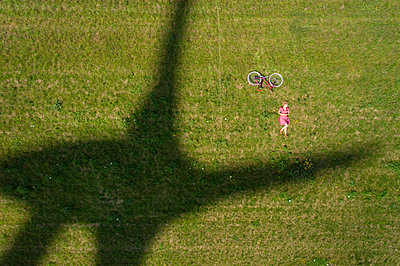 Girl and bicycle beside shadow of modern wind turbine - p429m2019464 by Mischa Keijser