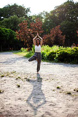 Young woman practicing yoga in park - p795m2199810 by JanJasperKlein