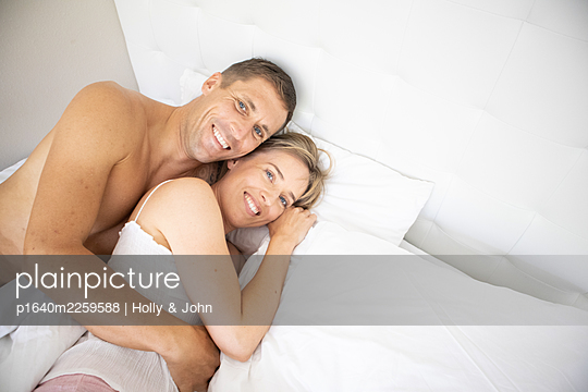 Couple in love cuddling in bed - p1640m2259588 by Holly & John