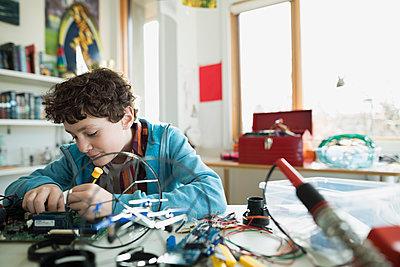 Focused boy assembling circuit board in bedroom - p1192m1129531f by Hero Images