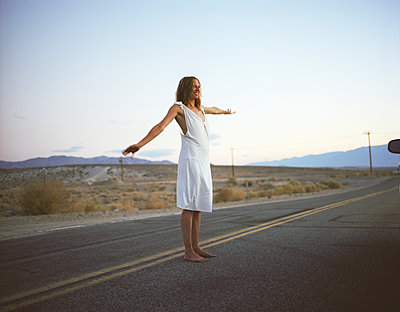 Woman standing with happy face on american road - p1610m2181507 by myriam tirler