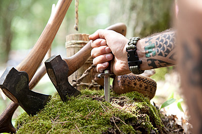 Axes, tree stump and hand holding knife in the forest - p300m1499359 by Michelle Fraikin