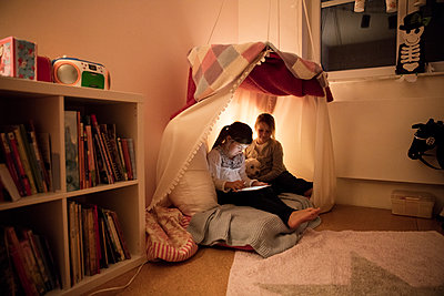 Two girls with dog and tablet in children's room - p300m1535431 by Robijn Page