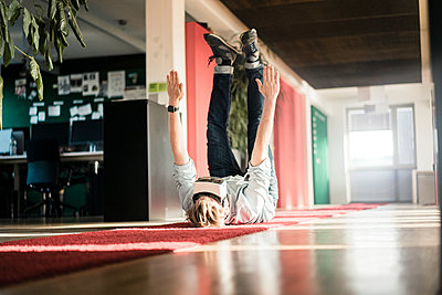 Businessman lying on carpet on the floor wearing VR glasses exercising - p300m1535502 by Joseffson