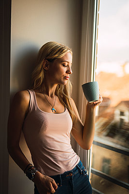 Blond young woman holding coffee mug at the window - p300m2042323 by Kike Arnaiz