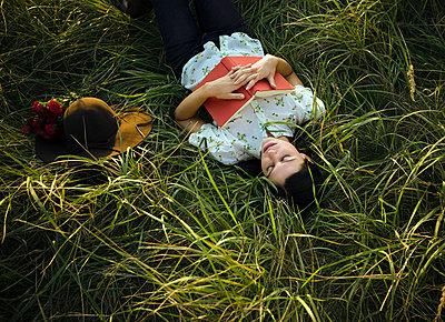 Woman sleeping in grass. - p4291438f by Chev Wilkinson