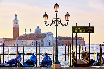 Gondolas on St Marks square waterfront with San Giorgio Maggiore church in background, Venice, Veneto, Italy - p429m2050962 by Fabio Muzzi