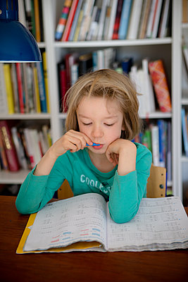 Girl does homework - p505m2169001 by Iris Wolf