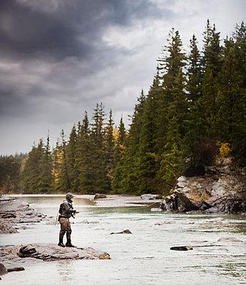 Caucasian man fishing at river - p555m1301793 by Mike Kemp