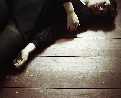 Young woman laying on floor - p956m1136855 by Anna Quinn