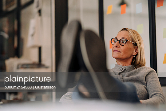 Mature businesswoman in office with feet on desk - p300m2154930 by Gustafsson