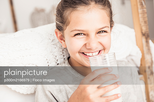 Portrait of happy girl drinking glass of milk - p300m2166979 by Floco Images