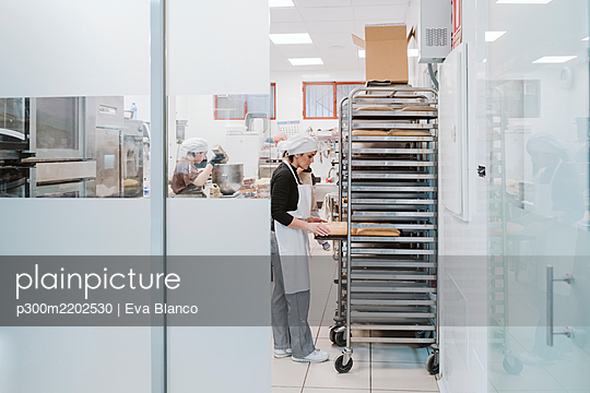 Male and female bakers working at bakery - p300m2202530 by Eva Blanco