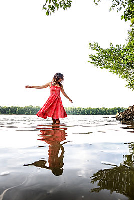 Woman in river, wearing summer dress - p1019m2098806 by Stephen Carroll