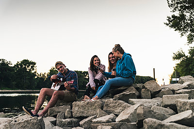 Group of friends sitting at the riverside in the evening - p300m2023781 by Uwe Umstätter