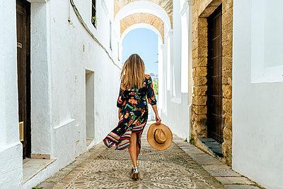 Spain, Cadiz, Vejer de la Frontera, back view of fashionable woman walking through passage - p300m2104147 by Kiko Jimenez