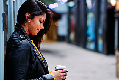 Smiling woman with disposable coffee cup leaning on wall - p300m2273655 by Angel Santana Garcia