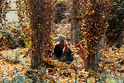Madrid, Spain. Young woman photographing in a forest and walking with her dog. - p300m2276045 von Manu Reyes