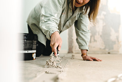 Woman putting cement on floor - p312m2207750 by Stina Gränfors
