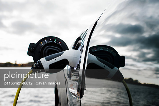 electric car charging socket and lead by the beach - p1166m2146612 by Cavan Images