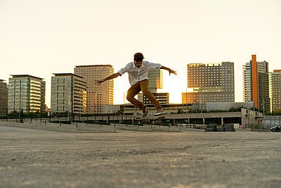 Young man doing a skateboard trick in the city at sunset - p300m2028720 by VITTA GALLERY
