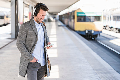Young businessman with cell phone and headphones at the train station - p300m2160723 by Uwe Umstätter
