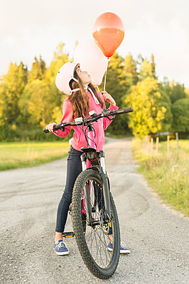 Sweden, Vastmanland, Hallefors, Bergslagen, Girl (10-11) riding bicycle at sunset - p352m1349603 by Sonia Jansson