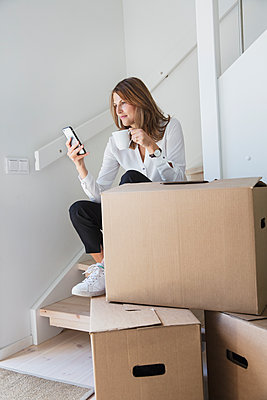 Woman sitting on staircase with smart phone and cardboard boxes - p352m2119269 by Helena Bonnevier