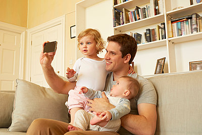 Mid adult man taking smartphone selfie with toddler and baby daughter on sofa - p429m1407932 by Emma Kim
