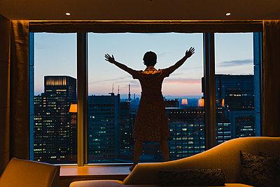 Frau blickt aus dem Fenster auf Tokio - p432m2116413 von mia takahara