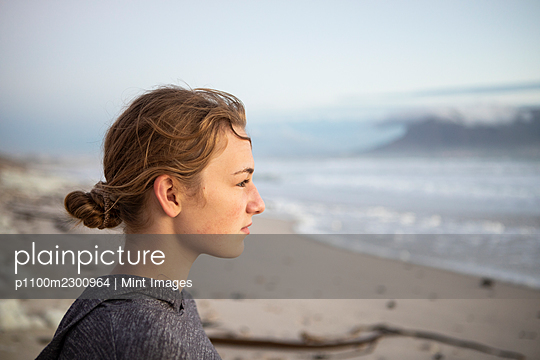 Profile portrait of a teenage girl looking out to sea from a beach at sunset. - p1100m2300964 by Mint Images