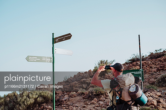 Hikers walking to the top of Guajara mountain with volcano Teide - p1166m2131172 by Cavan Images