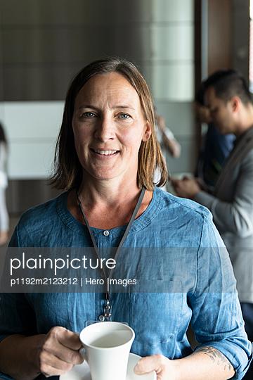 Portrait confident businesswoman enjoying conference coffee break - p1192m2123212 by Hero Images