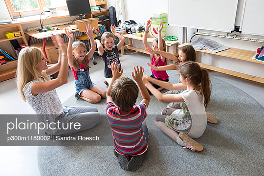 Teacher and pupils sitting in a circle on floor of their classroom raising hands