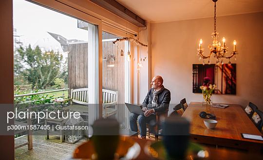 Senior man sitting at home, using laptop - p300m1587405 von Gustafsson