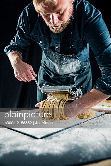 Hobby chef making fresh tagliatelle with pasta machine - p300m2156352 by Joseffson