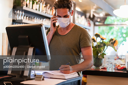 Restaurant manager with protective mask using computer and smartphone for reservation - p300m2202493 by Daniel Ingold