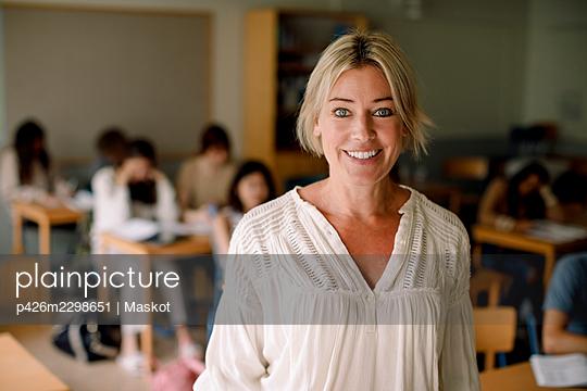 Portrait of smiling female teacher in classroom - p426m2298651 by Maskot