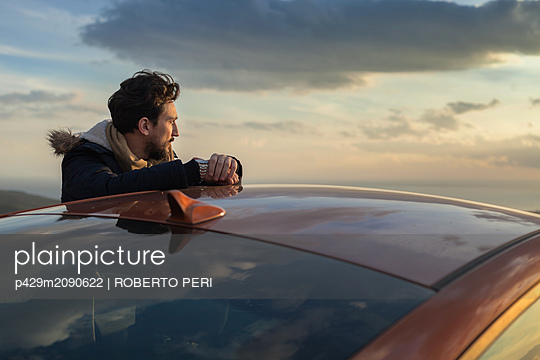 Man resting against car on roadside, enjoying view on hilltop - p429m2090622 by ROBERTO PERI