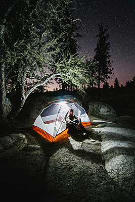 Hiker sitting in illuminated tent on rock by trees at night - p1166m1183045 by Cavan Images