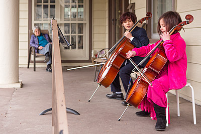 To children perform cello for elderly neighbor on front porch - p1166m2250667 by Cavan Images