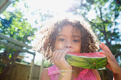 Portrait smiling girl eating watermelon in sunny backyard - p1192m1183953 by Hero Images