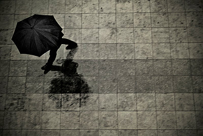 Man with umbrella  - p1445m2150456 by Eugenia Kyriakopoulou