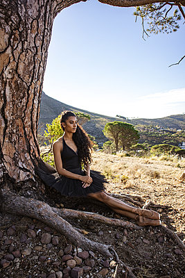 Brunette woman sitting under tree - p1640m2264344 by Holly & John