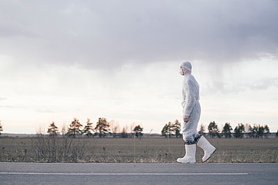 Man wearing protective suit and mask at the roadside of a country road - p300m2170145 by Ekaterina Yakunina