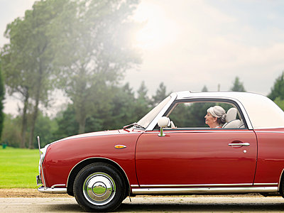 Senior woman driving along in red convertible - p429m895363f by Colin Hawkins
