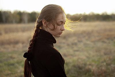 Pensive Caucasian woman standing in field - p555m1491169 by Vyacheslav Chistyakov